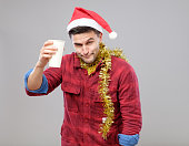 Funny young drunk man wearing Santa hat holding a paper cup. Studio shot on gray background. Concept of office christmas party