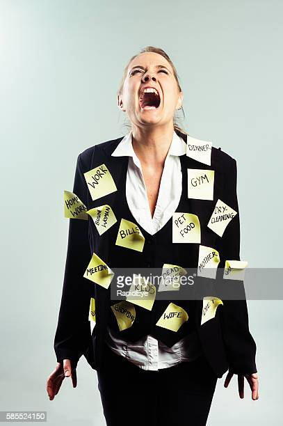 Furious and frustrated businesswoman covered in adhesive-note task reminders yells