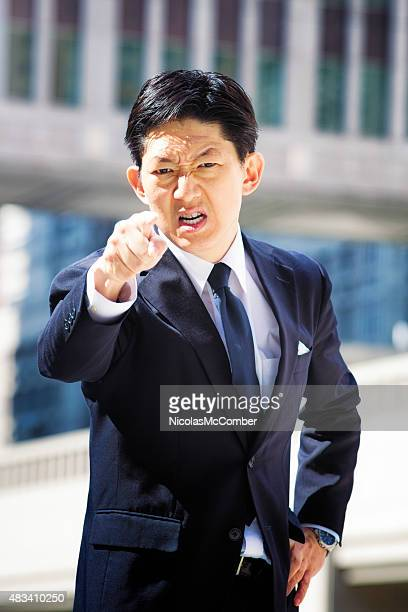 Furious angry Japanese office worker points and scowls