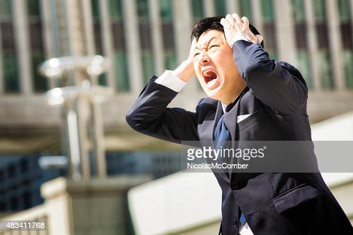 Furious angry Japanese office worker screams in despair : Stock Photo
