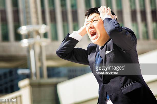 Furious angry Japanese office worker screams in despair