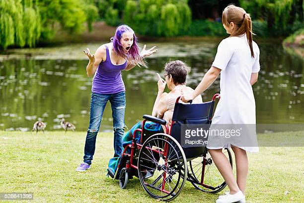 Furious argument between teenager and wheelchair-bound old woman,  nurse watching