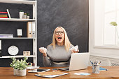 Deadline stress concept - furious business woman sitting at desktop in office and shouting. Female worker looking exhausted at workplace after hard working day, copy space