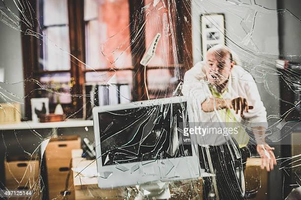 Furioso Uomo d'affari gettare il computer tramite una parete in vetro