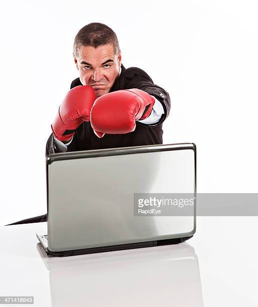 Furious businessman with boxing gloves and laptop attacks grimacing