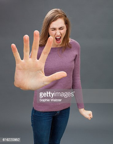 furious girl having tantrum, shouting in showing large hand forward : Stock Photo