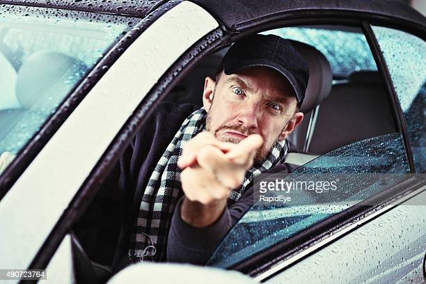 Furious man driving on rainy day points angrily through window