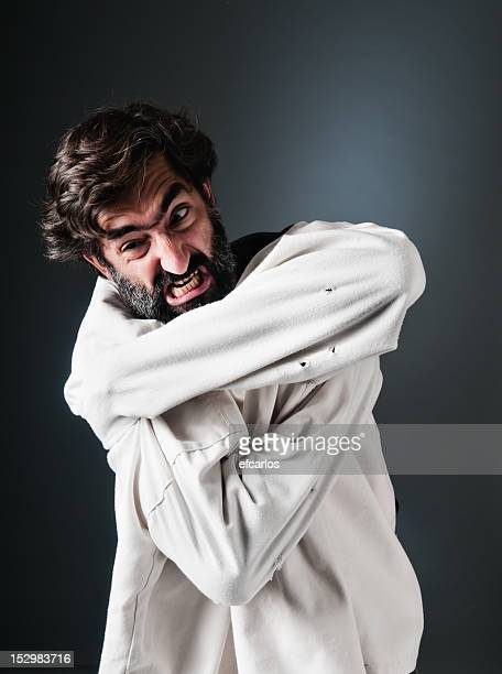 Furious man trying to scape from straitjacket