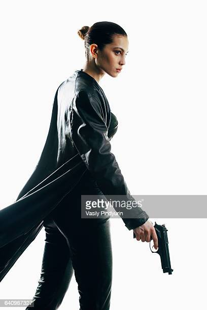 Furious spy holding gun walking against white background
