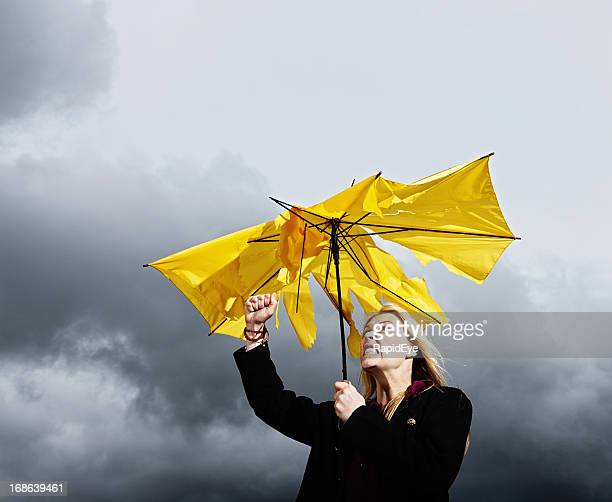 Furious woman shakes fist at storm that ruined her umbrella