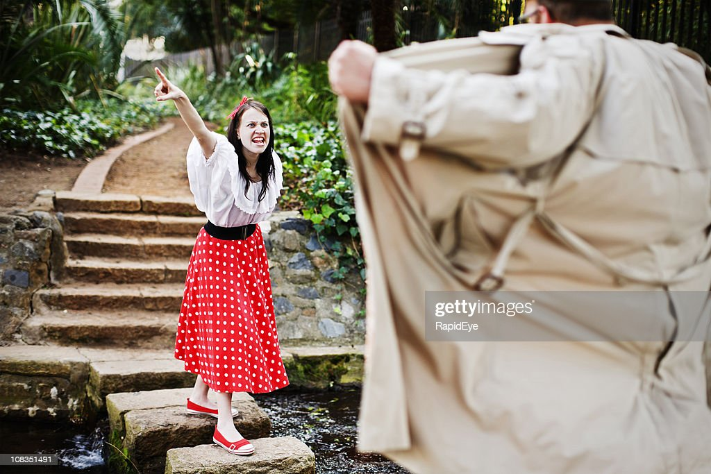 Furious young woman defies a flasher in the park : Stock Photo