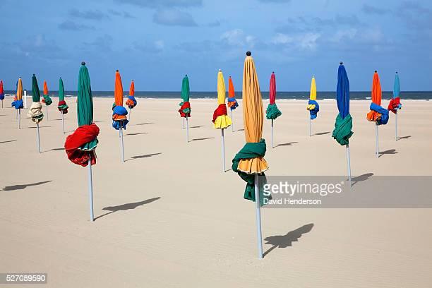 Furled beach umbrellas on beach, Deauville, France