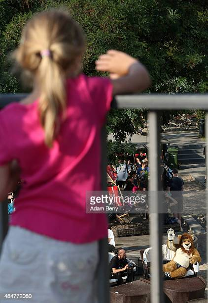 Furry enthusiast waves to a little girl at the Eurofurence 2015 conference on August 21 2015 in Berlin Germany Furry fandom a term used in zines as...