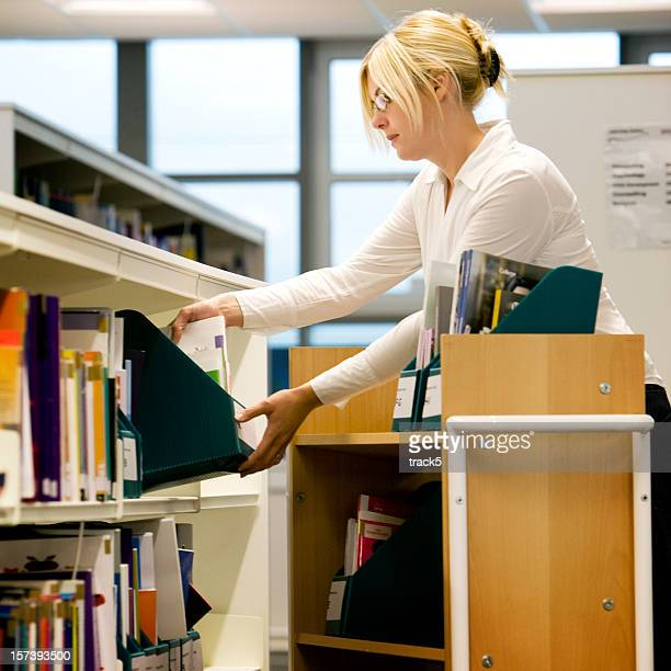 further education: librarian filing books on shelves