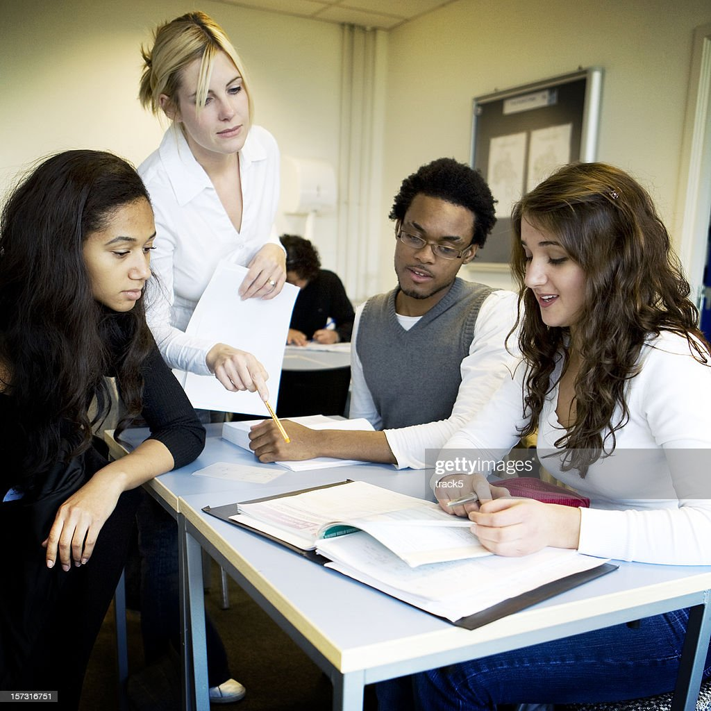 further education: teacher and college students working together in class : Stock Photo