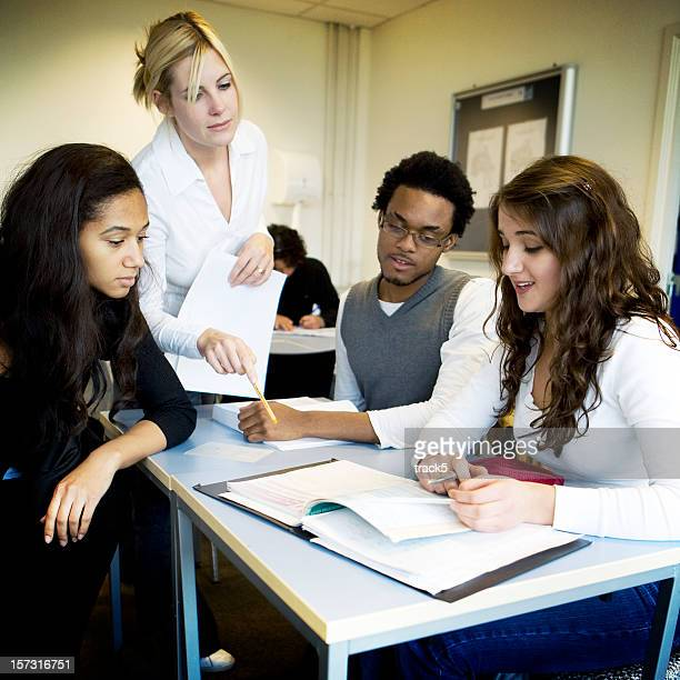 further education: teacher and college students working together in class