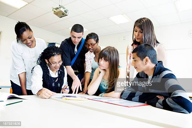 further education: teenagers working together with their teacher in class