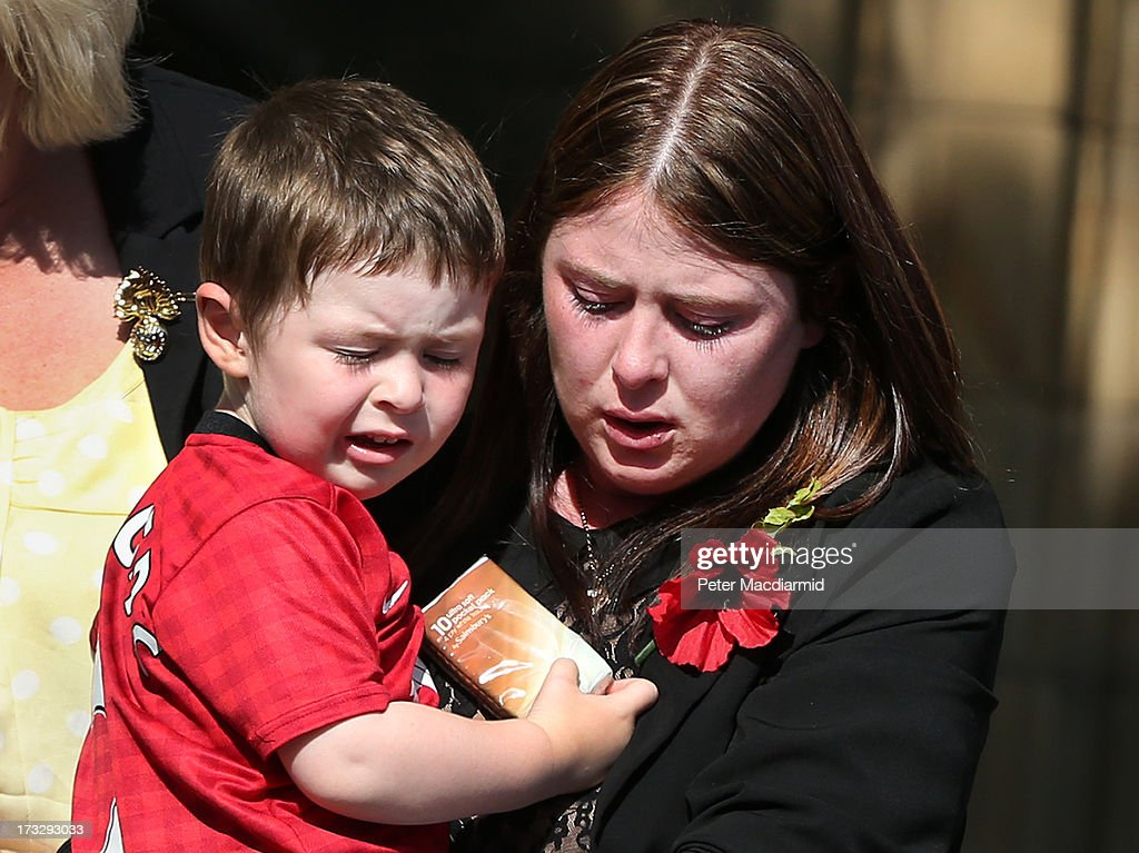 Fusilier Lee Rigby's wife Rebecca carries their son Jack from Bury Parish Church after attending the start of an overnight vigil on July 11 2013 in...