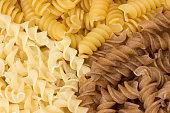 Three types of uncooked fusilli pasta.