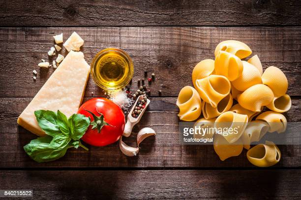 Fusilli pasta with ingredients on rustic wooden table