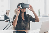 Confident young woman adjusting her virtual reality headset and smiling while sitting at her working place in office
