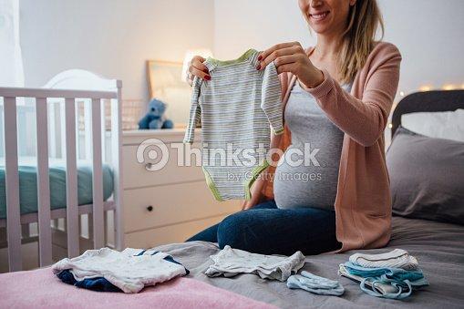 Future mom holds baby clothing : Stock Photo