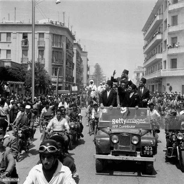 Future Tunisian President and NewDestour nationalist party leader Habib Ben Ali Bourguiba standing atop a Land Rover jeep and surrounded by his...