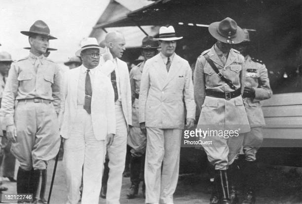 Future US President Dwight Eisenhower and General Douglas MacArthur walk with unidentified others Philippines mid 1930s