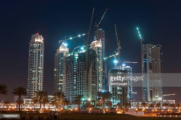 Futuristic high rise construction skyscrapers at night Dubai