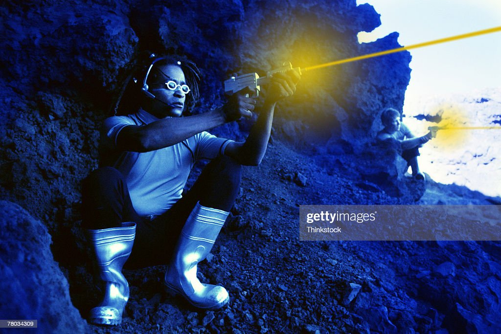 Futuristic man shooting laser gun from rocks