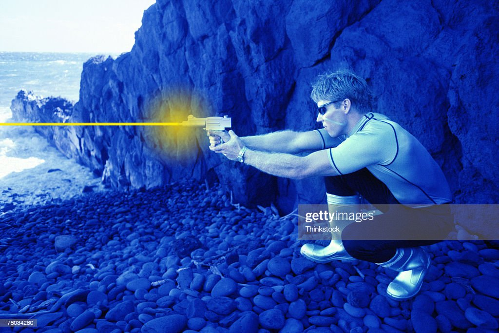 Futuristic man shooting laser gun on rocky shore