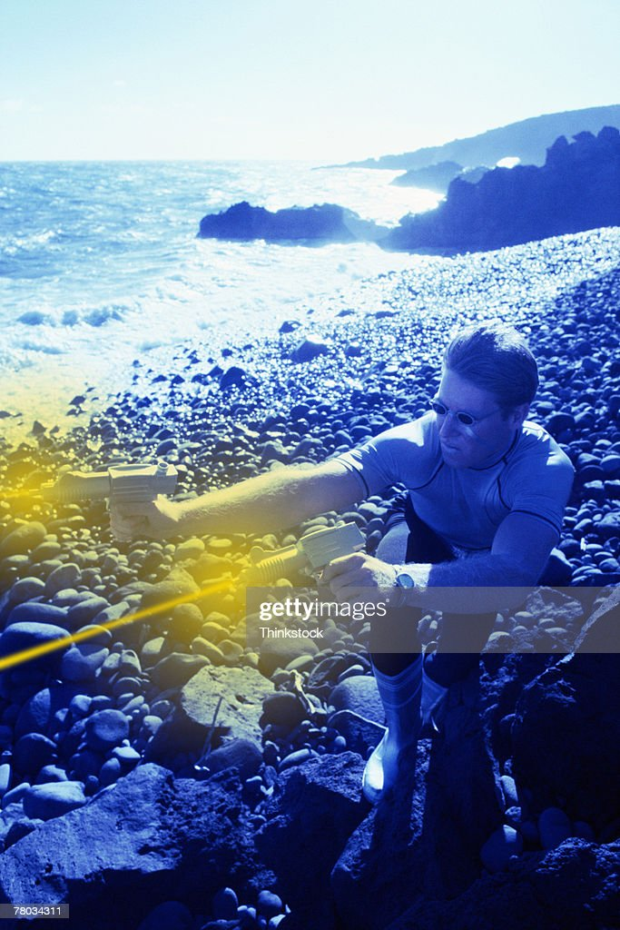 Futuristic man shooting laser guns on rocky shore