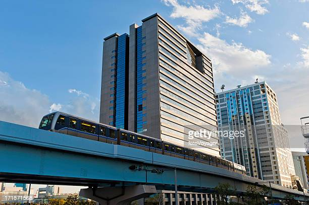 Futuristic monorail train rushing through city skyscrapers Odaiba Tokyo Japan