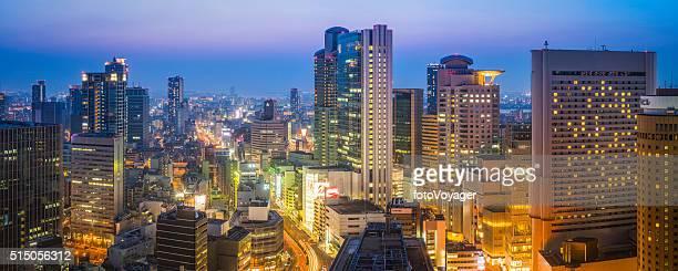 未来的な高層ビル、ネオンの夜の街並みのパノラマに広がるサンセット梅田オサカ日本
