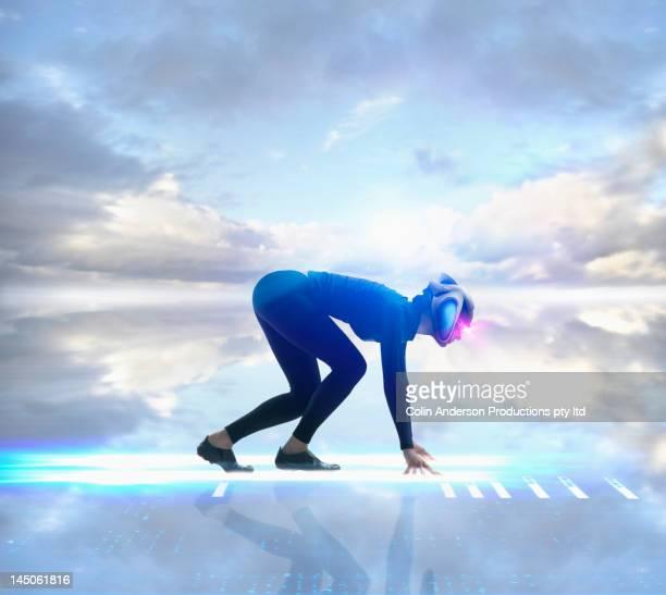 Futuristic Pacific Islander woman crouching at start of race