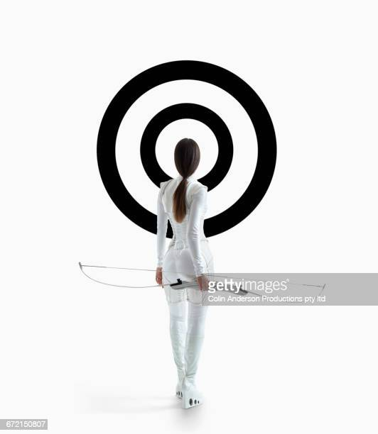 Futuristic Pacific Islander woman holding bow at target