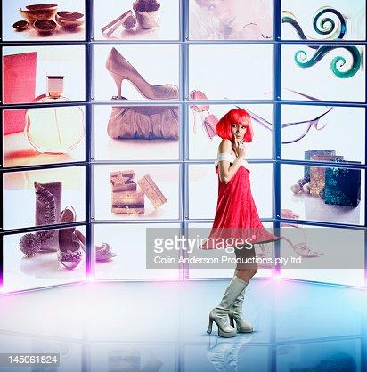 Futuristic Pacific Islander woman looking at television screens : Foto de stock