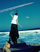 Futuristic woman by seaside, rocket across skyline (Digital Composite)