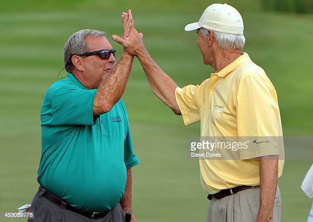 Fuzzy Zoeller and Andy North celebrate after Zoeller sank a put on the 17th hole as part of the 'Greats of Golf' competition during the second round...