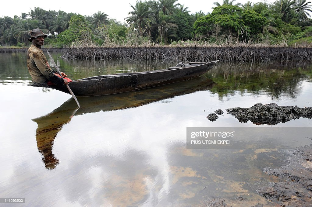 Gaagaa Gidom, a 60 year-old fisherman and father of eight looks at the spilled crude oil floating on his shadow in the waters of the Niger Delta swamps of Bodo, a village in the famous Nigerian oil-producing Ogoniland, which hosts the Shell Petroleum Development Company (SPDC) in Nigeria's Rivers State on June 24, 2010. The region has in recent years experienced an average 300 spills a year, roughly one spill a day, from terminals, pipes and platforms, according to government officials and experts. Sabotage of oil facilities by armed rebels fighting a fairer share of oil wealth for locals and theft of crude, popularly known as oil bunkering in recent years saw spills spiking to new levels.