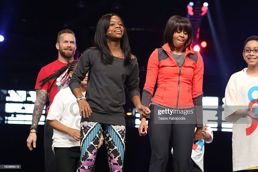 Gabby Doulas (L) and first lady <a gi-track='captionPersonalityLinkClicked' href=/galleries/search?phrase=Michelle+Obama&family=editorial&specificpeople=2528864 ng-click='$event.stopPropagation()'>Michelle Obama</a> (R) dances with school children during a debut of a school exercise program February 28, 2013 in Chicago, Illinois. Obama unveiled a new program called 'Let's Move Active Schools' to help schools create a physical activity programs for students.