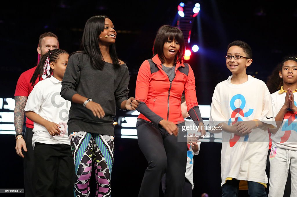 Gabby Doulas (L) and first lady <a gi-track='captionPersonalityLinkClicked' href=/galleries/search?phrase=Michelle+Obama&family=editorial&specificpeople=2528864 ng-click='$event.stopPropagation()'>Michelle Obama</a> (C) dances with school children during a debut of a school exercise program February 28, 2013 in Chicago, Illinois. Obama unveiled a new program called 'Let's Move Active Schools' to help schools create a physical activity programs for students.