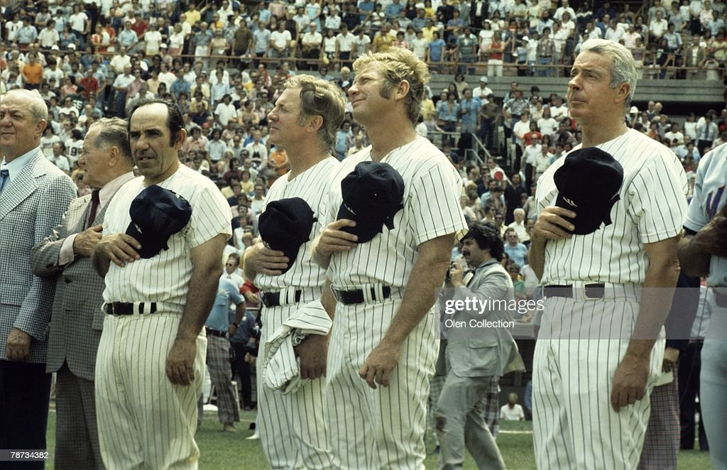 Gabe Paul, Joe McCarthy, Yogi Berra #8, Whitey Ford #16, Mickey Mantle #7 and Joe Dimaggio #5 of the New York Yankees hold their hats over their hearts as the national anthem is played during Old Timers Day ceremonies prior to a game on August 3, 1974 between the Boston Red Sox and the New York Yankees at Yankee Stadium in New York, New York. 740803-18