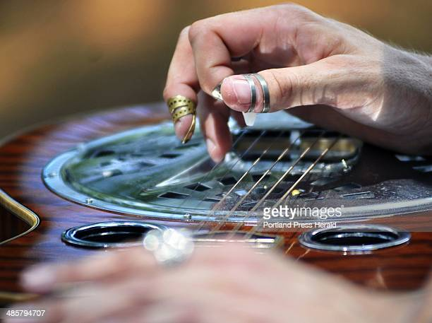 Chad Graves a dobro player with the bluegrass band The Hillbenders from Springfield Mo practices under a tree away from the stage before playing his...