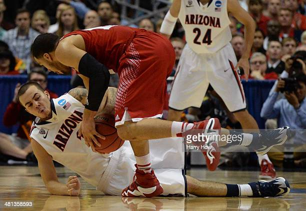 Gabe York of the Arizona Wildcats dives for a loose ball against Traevon Jackson of the Wisconsin Badgers in the first half during the West Regional...