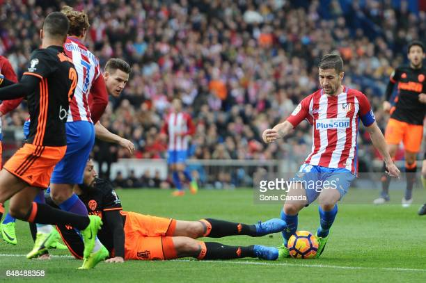 Gabi #14 of Atletico de Madrid and Ezequiel Garay #24 of Valencia CF during The La Liga match between Atletico Madrid v Valencia CF at Vicente...