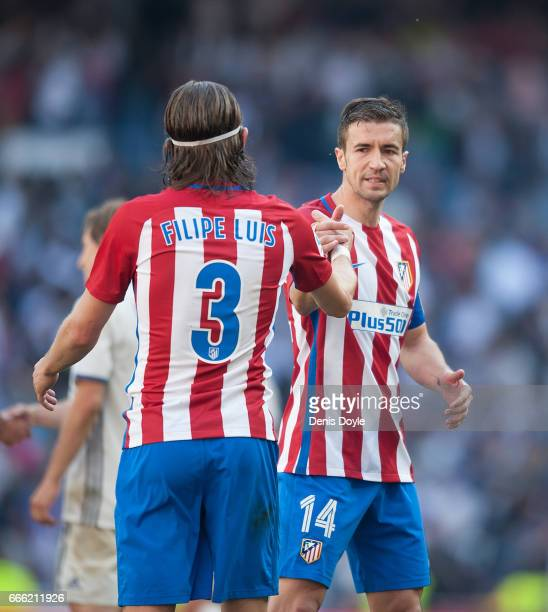 Gabi Fernandez of of Club Atletico de Madrid shakes hands with teamate Felip Luis at the end of the La Liga match between Real Madrid CF and Club...