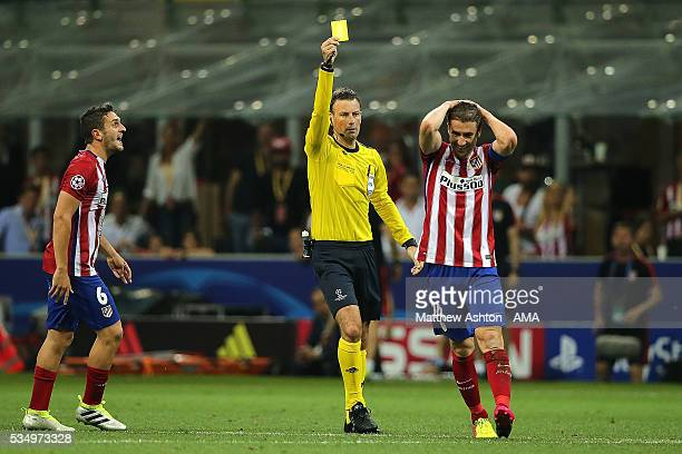 Gabi of Atletico Madrid is booked by Referee Mark Clattenburg during the UEFA Champions League final match between Real Madrid and Club Atletico de...