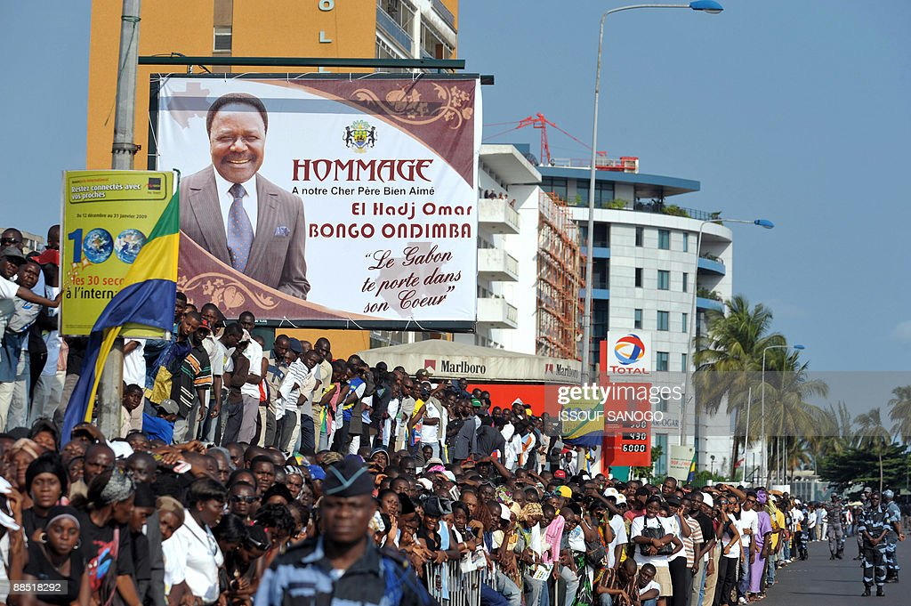 Gabonese wait under a huge poster of late Gabonese President Omar Bongo in a street of Libreville on June 16 2009 during his funeral More than a...