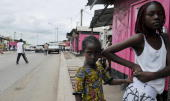 Gabonese youths stand outside a shop in Libreville on September 6 as life returns to normal after the recent postpresidential election violence...